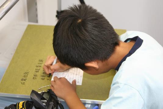 Тцун Минг подписывает свой рисунок для Джеки Чана